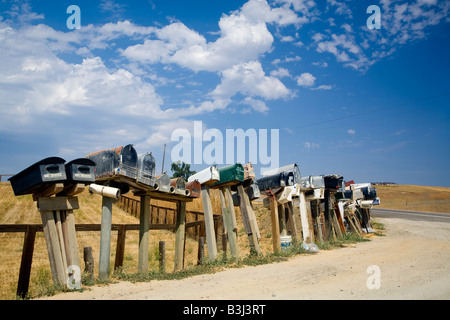 Long shot of a row of mailboxes in the rural Central Valley of California USA against a deep blue sky - Stock Photo
