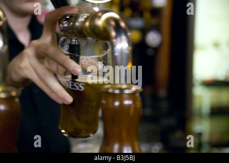 Bartender pouring a pint of Guinness in a pub. - Stock Photo
