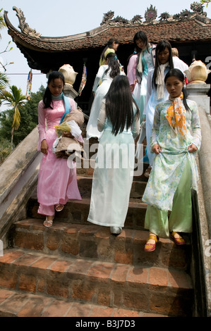 A group of Vietnamese girls wearing the traditional Ao Dai costume descending the steps of the One Pillar Pagoda - Stock Photo