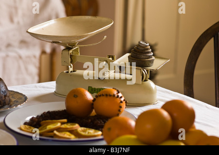Old-fashioned weighing scales with oranges in a Victorian kitchen - Stock Photo