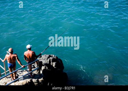 Old men fishing in waters in front of the Paseo de San Telmo, Puerto de la Cruz, Tenerife, Canary Islands - Stock Photo