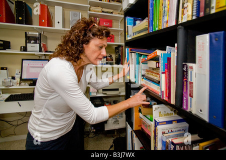 A 50 year old self employed woman works in her home office in Mission Viejo California - Stock Photo