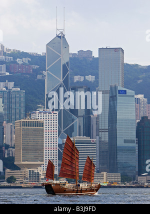 Traditional Chinese Junk sailing at the Victoria harbour with the Hong Kong skyline in background - Stock Photo