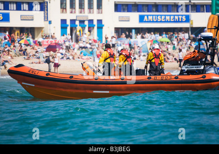 RNLI rescue boat B-803 'William Hurst' and crew in action off the crowded Bournemouth beach, Dorset. UK. - Stock Photo