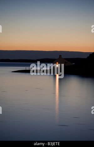 A bright window light shines across the still Loch Bay from a remote house at Stein, Waternish Point on the Isle - Stock Photo