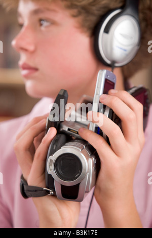 Young boy wearing headphones in bedroom holding many electronic devices - Stock Photo