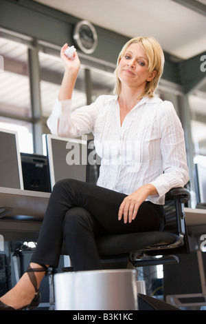 Businesswoman in office space throwing garbage in bin - Stock Photo