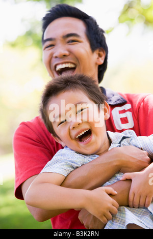Man and young boy outdoors embracing and smiling - Stock Photo