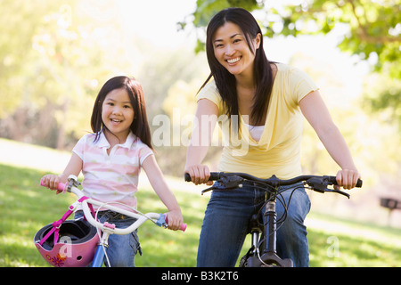 Woman and young girl on bikes outdoors smiling - Stock Photo