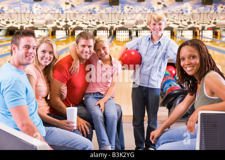 Family in bowling alley with two friends smiling - Stock Photo
