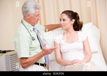 Doctor giving woman checkup in exam room - Stock Photo