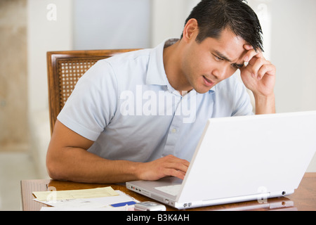 Man in dining room using laptop and frowning - Stock Photo