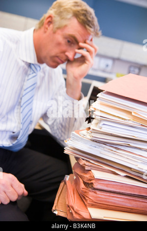 Businessman in cubicle with laptop and stacks of files - Stock Photo