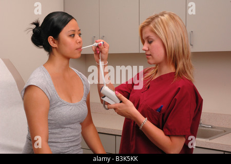 Nurse or medical assistant taking patient temperature - Stock Photo