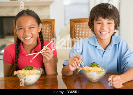 Two young children eating Chinese food in dining room smiling Stock Photo