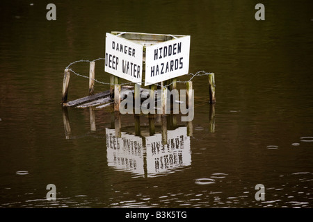 A sign in a quarry in County Durham, England, warns of deep water and hidden hazards. - Stock Photo