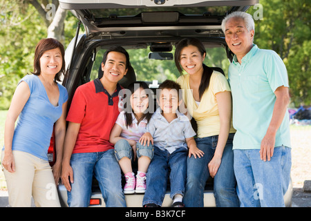 Extended family sitting in tailgate of car - Stock Photo