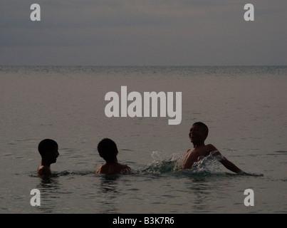 Three boys playing in the sea off Koh Samui - Stock Photo