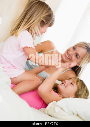 Woman and two young girls in bed playing and smiling - Stock Photo