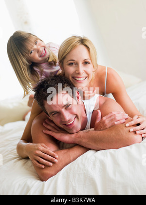 Family in bed playing and smiling - Stock Photo