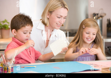 Woman and two young children in kitchen with art project smiling - Stock Photo
