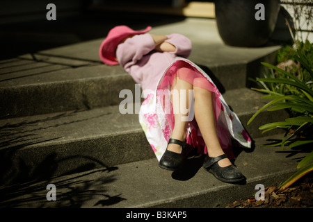 Five year old girl relaxes on steps in spring sunshine - Stock Photo