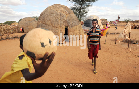 Idle Abdi Lahi 12 holding ball and Mohammed Nor Abdi at Belet Amin IDP (Internally Displaced People) camp, Somalia. - Stock Photo