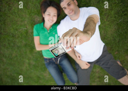 young couple taking of digital picture of themselves laying in the grass outdoors - Stock Photo