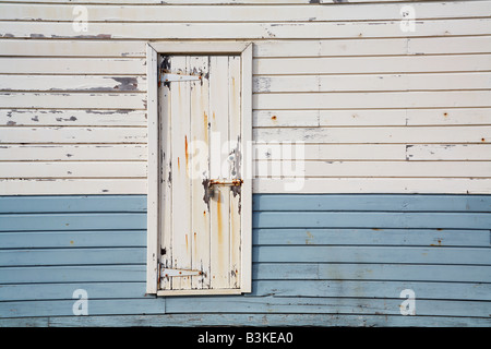 padlocked wooden door in a wooden wall - Stock Photo