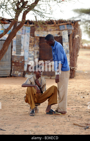 Abdiwah Hassan Abdi 17 getting his hair cut by Mowhid Mahmod Moge barber at Belet Amin a camp for internally displaced - Stock Photo