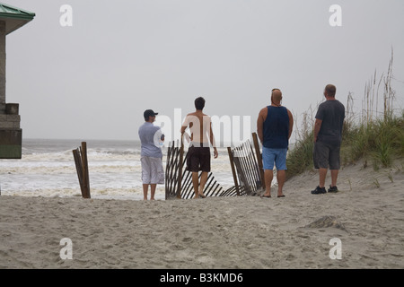 Four young men watch the surf at Jacksonville Beach Florida while Tropical Storm Hanna is passing by September 5th - Stock Photo