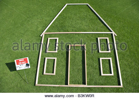 """For sale"" sign and house outline in grass - Stock Photo"