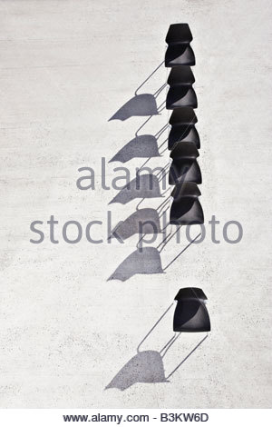 Single chair separated from line of office chairs - Stock Photo