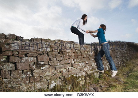 Teenage girl helping friend over rock wall - Stock Photo