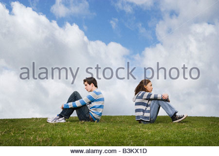 Teenage couple turned away from one another in field - Stock Photo