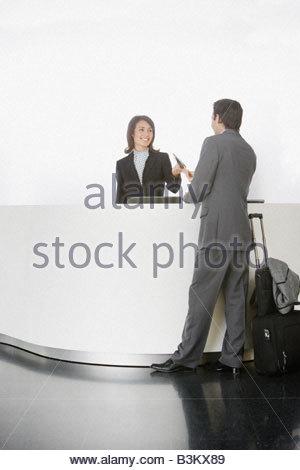 Businesswoman greeting businessman at reception desk - Stock Photo