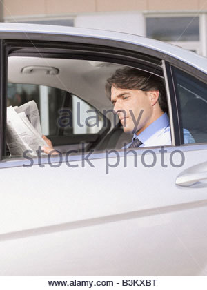 Businessman reading newspaper in back seat of car - Stock Photo