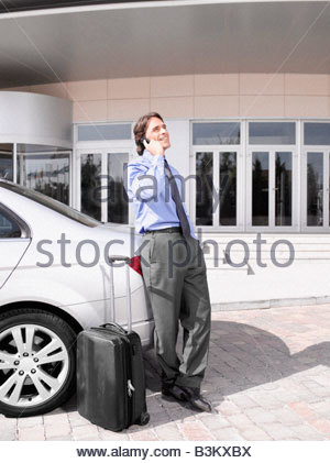 Businessman with suitcase talking on cell phone - Stock Photo