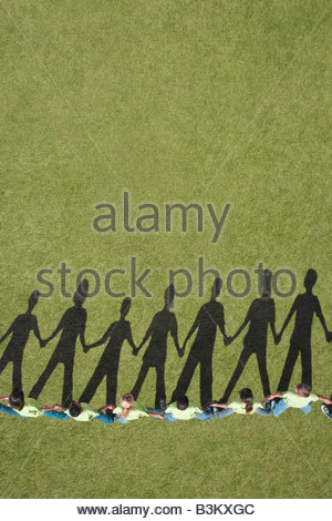 Shadow on grass of children holding hands - Stock Photo