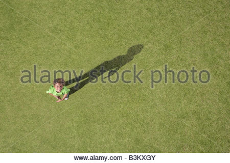 Boy standing in grass looking up - Stock Photo