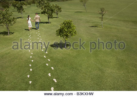Couple walking through field trailing footprints - Stock Photo