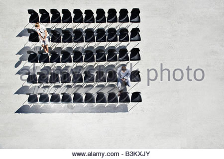 Businesspeople sitting in office chairs on sidewalk - Stock Photo