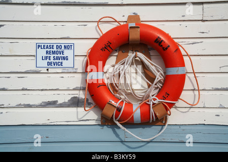 life belt hanging on a wall with associated sign - Stock Photo