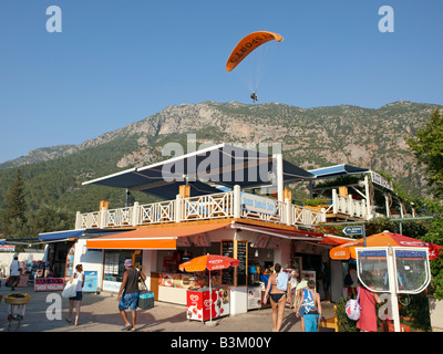 Paraglider flying above the popular Buzz Bar in the village of Oludeniz. Province of Mugla, Turkey. - Stock Photo