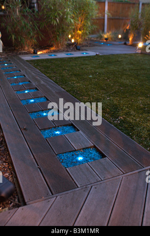 decking path lit by blue glass lights in modern garden - Stock Photo