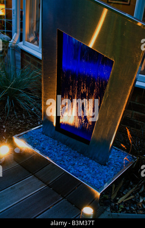 blue metal and glass lit water feature in modern landscaped garden - Stock Photo