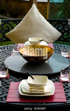 outdoor dining set in modern landscaped garden - Stock Photo