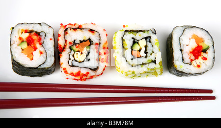 Japanese nori wrapped futomaki at each end and rice wrapped uramaki California roll suchi rolls on a plate with - Stock Photo