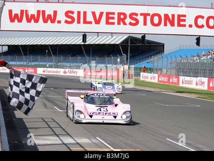 Mike Wilds  in No.43 a 1989 Pink/White/Italya Sports, Porsche 962 crossing the finish line - Stock Photo