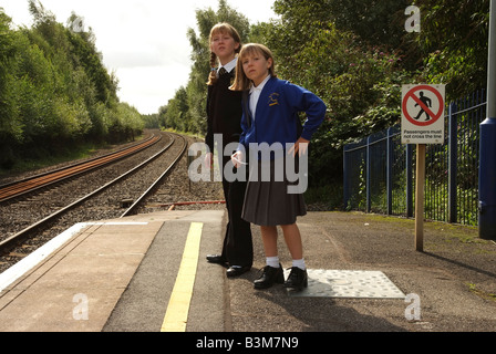 Young girls waiting for their train on a railway station platform Travelling to and from school - Stock Photo